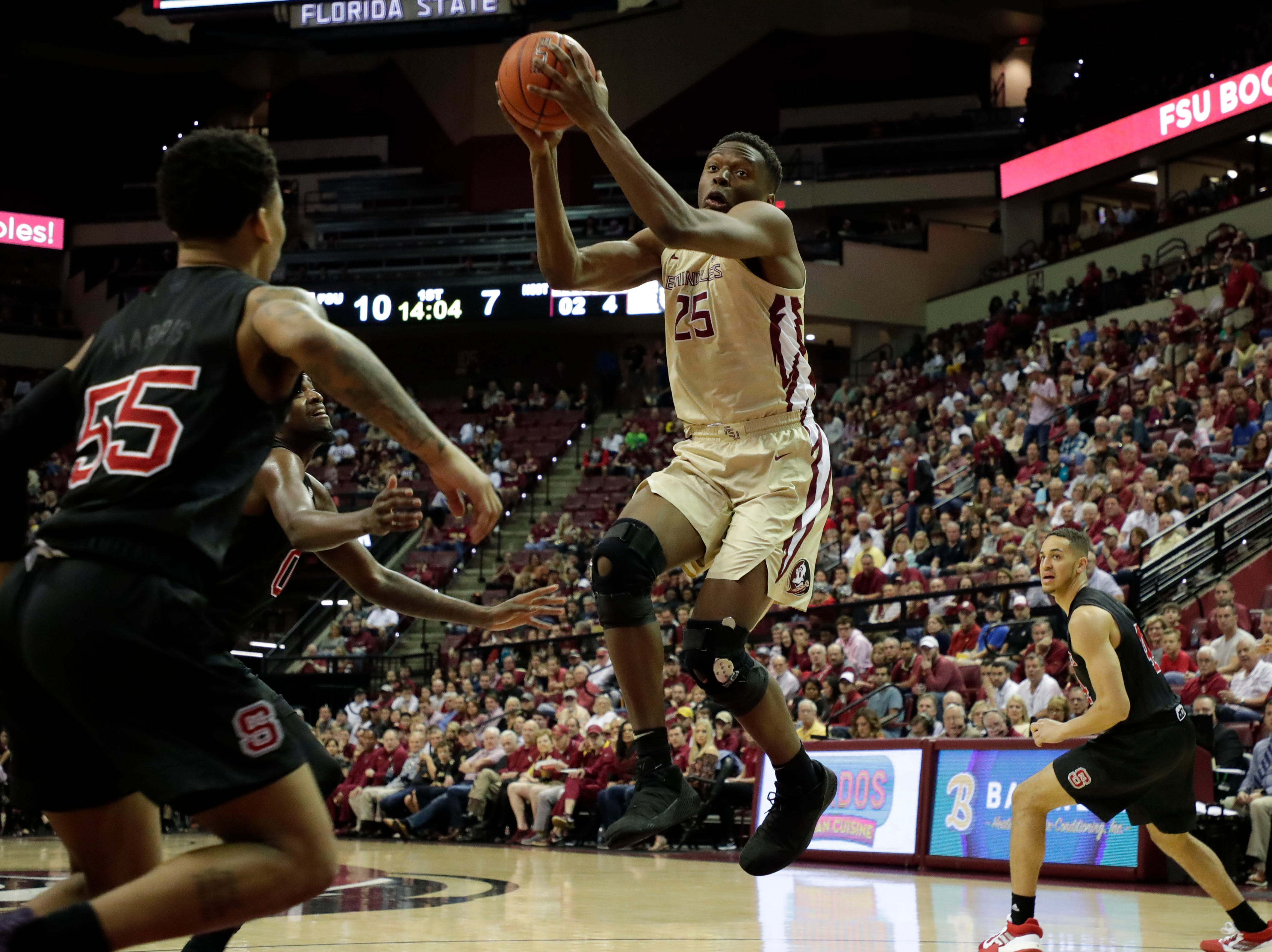 Florida State Seminoles forward Mfiondu Kabengele (25) catches a pass from Florida State Seminoles guard David Nichols (11). The Florida State Seminoles host the NC State Wolfpack at the Tucker Civic Center Saturday, March 2, 2019.