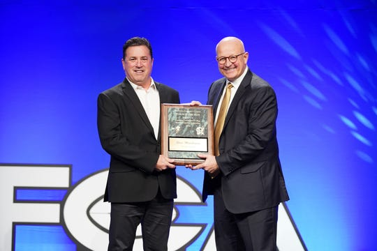 Ventura College football coach Steve Mooshagian, left, accepts the ACCFCA national Coach of the Year award from Wyoming head coach Craig Bohl in San Antonio.