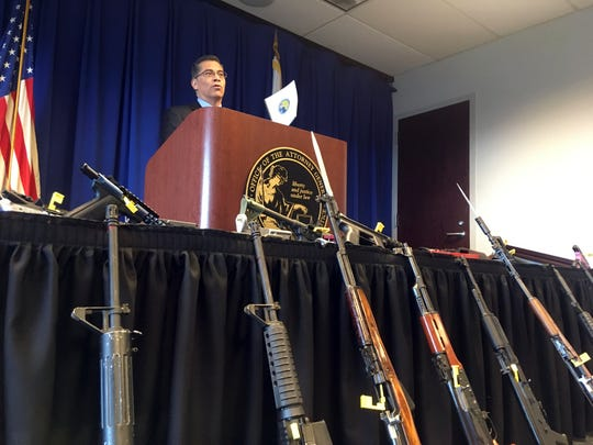 Attorney General Xavier Becerra speaks in front of a cache of seized firearms at a news conference Friday in Sacramento, Calif. Becerra unveiled new numbers for 2018 Friday from a uniquely California program that seizes guns from people no longer allowed to own them because of criminal convictions or mental illness.