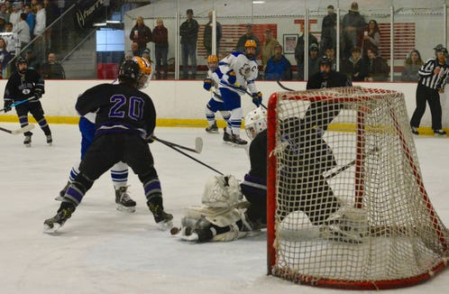 John Jay goalie Eric Sasimovich makes a save during the third period of Saturday's regional championship game against West Seneca West at Brewster Ice Arena. Teammate Charlie Oestreicher is defending to the left.
