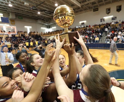 Ossining players celebrate with the gold ball after defeating Ursuline 78-67 in the girls basketball Class AA section final at Pace University in Pleasantville on Saturday, March 2, 2019.