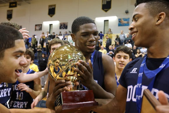 Dobbs Ferry's Damani Fraser celebrates with the gold ball after winning the Class B championship game at Pace University March 1, 2019. Dobbs Ferry beat Blind Brook 50-45 in OT.