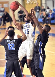 Shaft Clark of Caesar Rodney goes up for a shot between a pair of St. George's defenders in the second half..  GARY EMEIGH/Special To The News Journal
