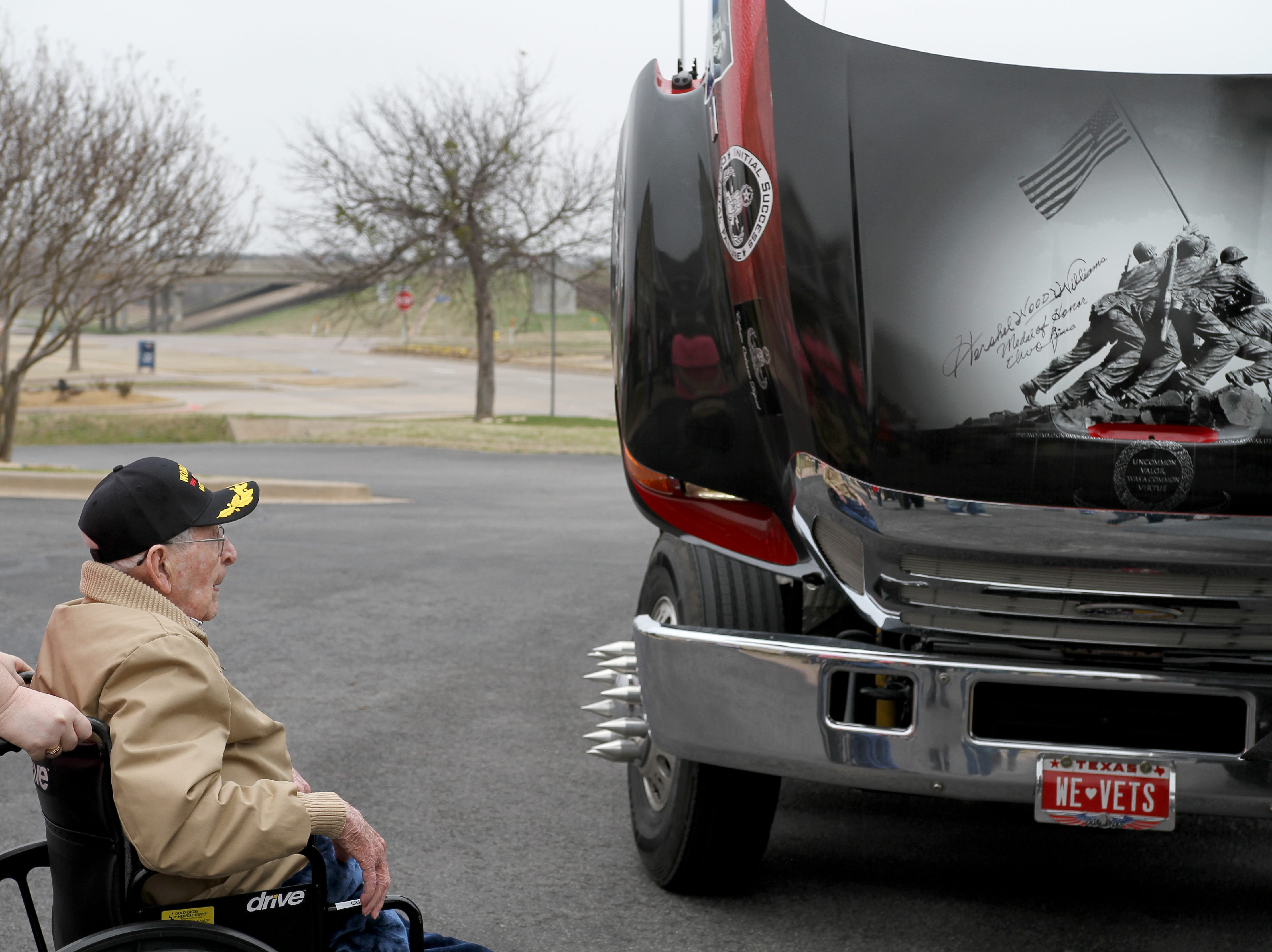 WWII veteran Joe Cuba signs the hood of a truck at his 100th birthday party Saturday, March 2, 2019, at Brookdale Midwestern.
