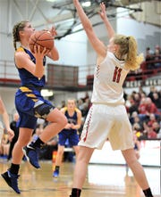 Maysville's Bailee Smith goes up for a shot in the first half against New Philadelphia's Paige Kaiser. The Panthers lost 54-50 in Saturday's district final.