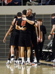 Waverly senior Ethan Dunn receives a hug from an assistant coach during the fourth quarter of the Tigers' 65-45 loss to Sheridan in a Division II district semifinal at Ohio University.