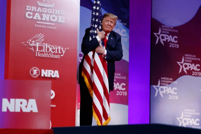 President Donald Trump hugs the American flag as he arrives to speak at Conservative Political Action Conference on March 2 in Oxon Hill, Maryland.