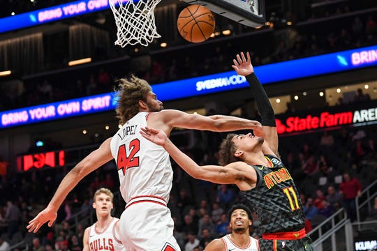 Atlanta Hawks guard Trae Young (11) tries to recover the ball against Chicago Bulls center Robin Lopez (42) during the first half at State Farm Arena.
