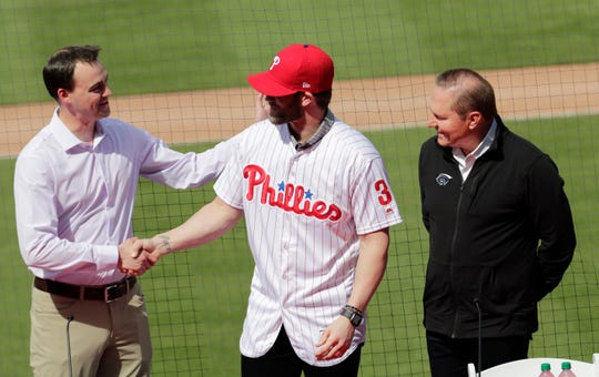 Philadelphia Phillies general manager Matthew Klentak, left, shakes hands with Bryce Harper, center, as agent Scott Boras looks on during a news conference at the Phillies spring training baseball facility, Saturday, March 2, 2019, in Clearwater, Fla. Harper and the Phillies agreed to a $330 million, 13-year contract, the largest deal in baseball history.