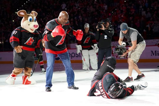 Carolina Hurricanes left wing Jordan Martinook (48) is knocked out by Evander Holyfield during their celebration after beating the St. Louis Blues.