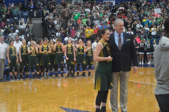 Hicks freshman Lauren Quinn (left) receives the MVP trophy from LHSAA Executive Director Eddie Bonine.