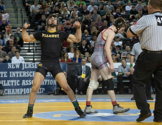 St. John Vianney's Dean Peterson celebrates after winning the 113-pound state championship and becoming St. John Vianney's first state wrestling champion.