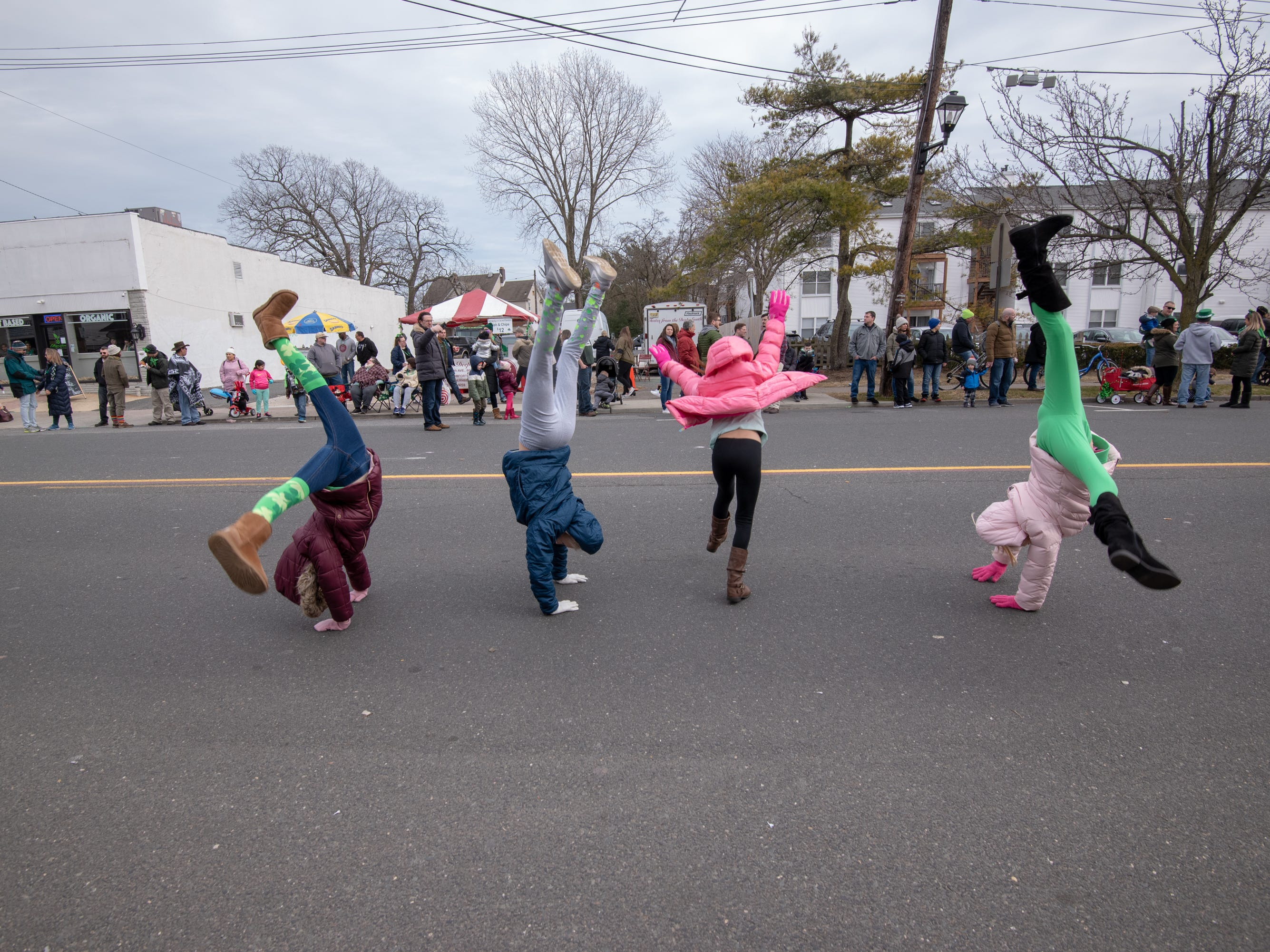 Four friends from Jackson Twp., do cartwheels. The annual St Patrick's Day Parade was held in Belmar, NJ, today, Sunday, March 3, 2019. / Russ DeSantis for the Asbury Park Press