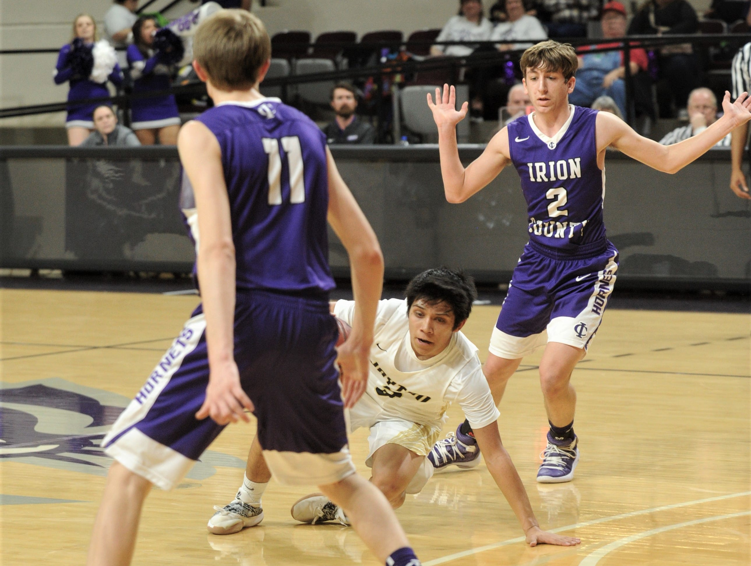 Jayton's Aaron Hernandez, center, falls to the court but keeps possession of the ball as Irion County's Kaden Coucilman (2) and Dawson Sparks defend. The Jaybirds beat Irion County 47-32 in the Region II-1A championship game Saturday, March 2, 2019, at Abilene Christian's Moody Coliseum.