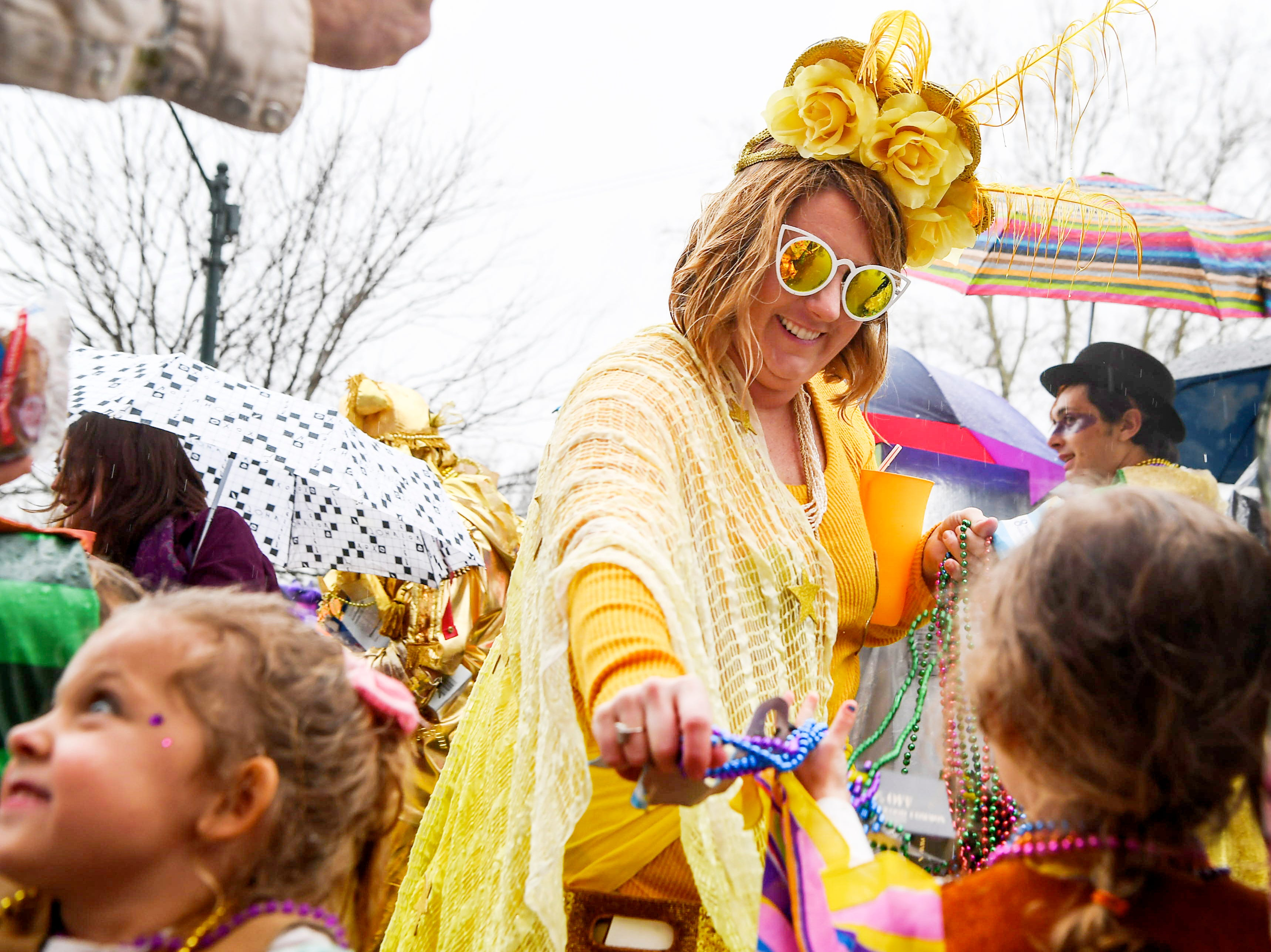 Tayler Sanders-Kyser hands out beads during the 12th annual Mardi Gras Parade March 3, 2019 in Asheville.