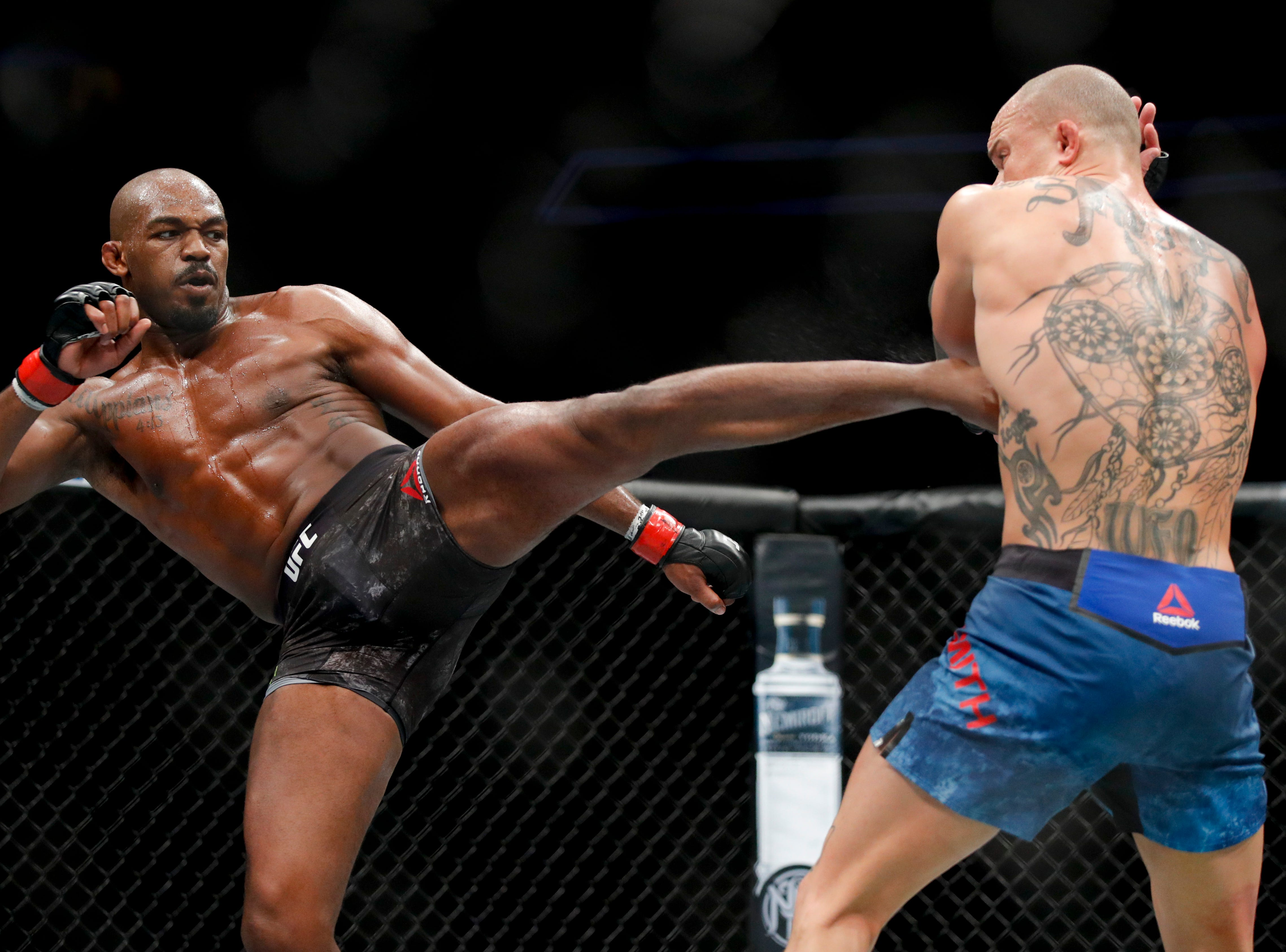 Jon Jones, left, kicks Anthony Smith during a light heavyweight mixed martial arts title bout at UFC 235, Saturday, March 2, 2019, in Las Vegas. (AP Photo/John Locher)