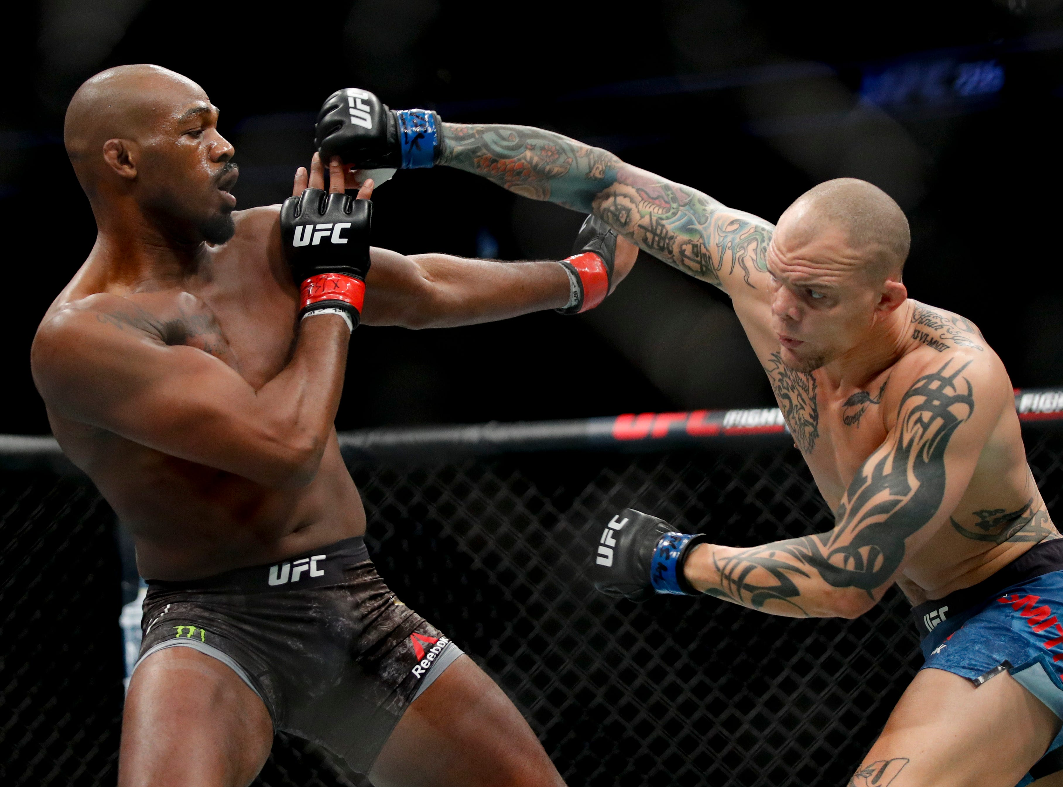 Jon Jones, left, fights Anthony Smith in a light heavyweight mixed martial arts title bout at UFC 235, Saturday, March 2, 2019, in Las Vegas. (AP Photo/John Locher)