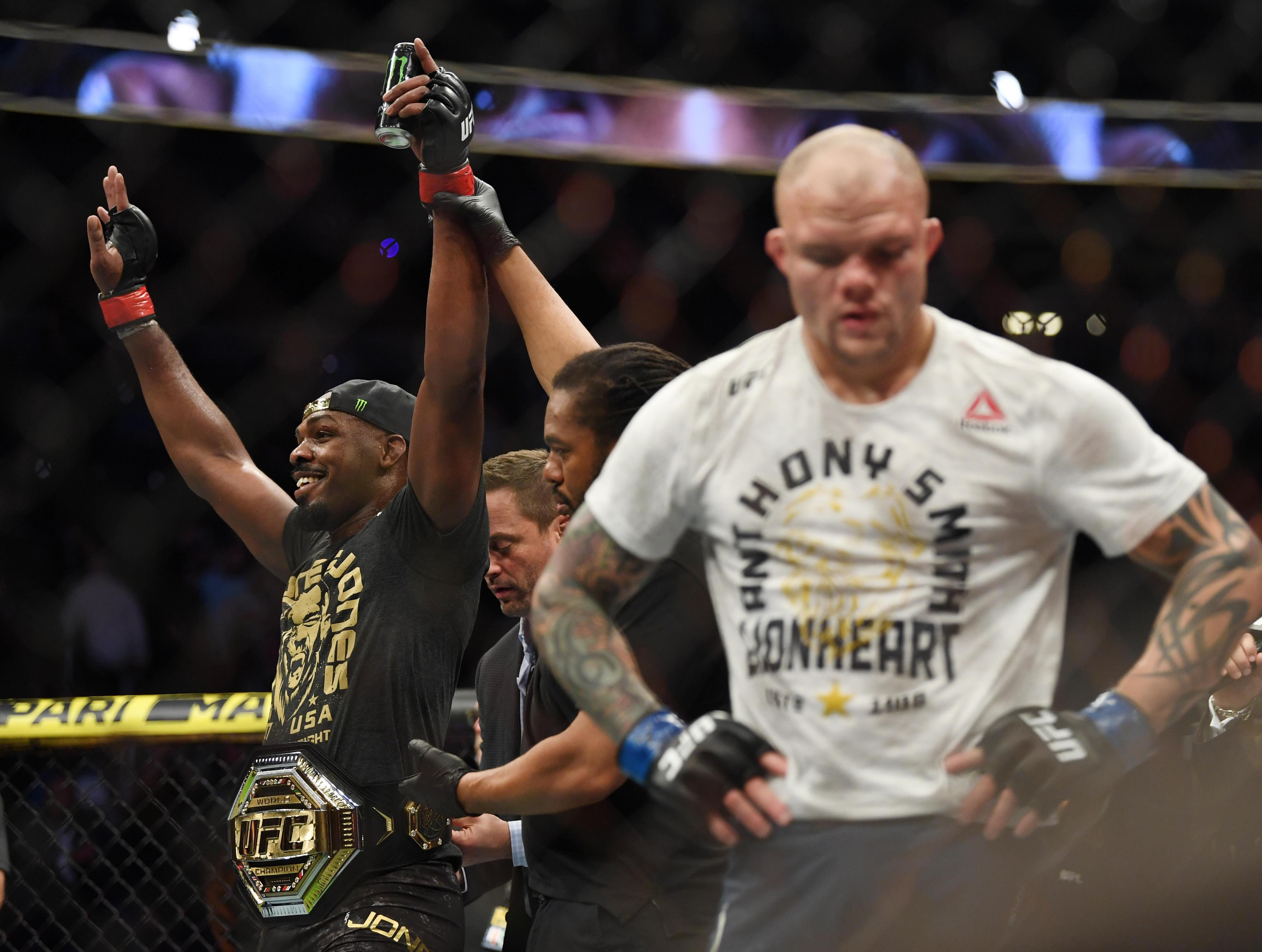 Mar 2, 2019; Las Vegas, NV, USA; Jon Jones (red gloves) with the title belt after defeating Anthony Smith (blue gloves) during UFC 235 at T-Mobile Arena. Mandatory Credit: Stephen R. Sylvanie-USA TODAY Sports