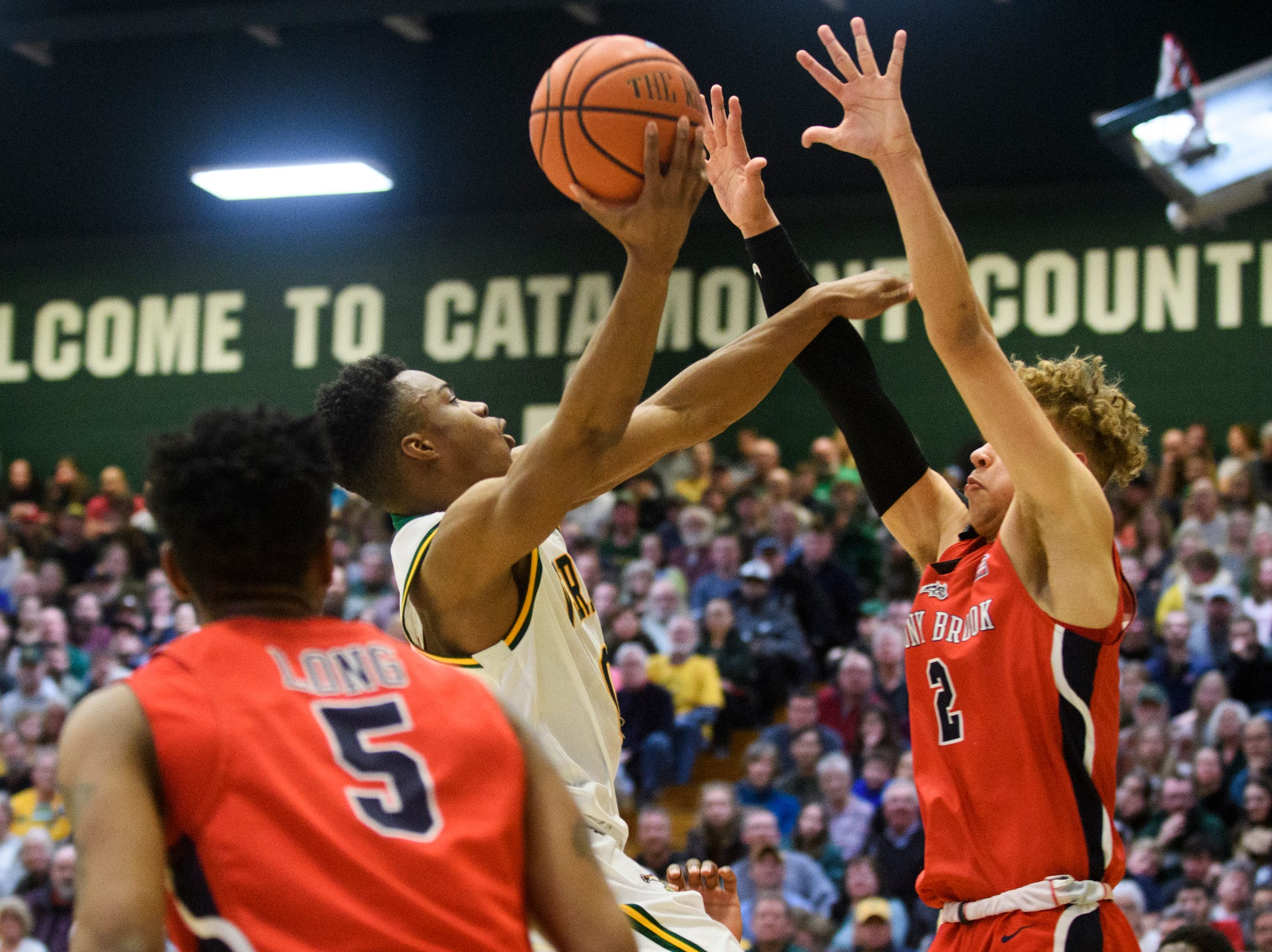 Vermont guard Stef Smith (0) leaps for a basket over Stony Brook's Miles Latimer (2) during the men's basketball game between the Stony Brook Seawolves and the Vermont Catamounts at Patrick Gym on Saturday night March 2, 2019 in Burlington, Vermont.