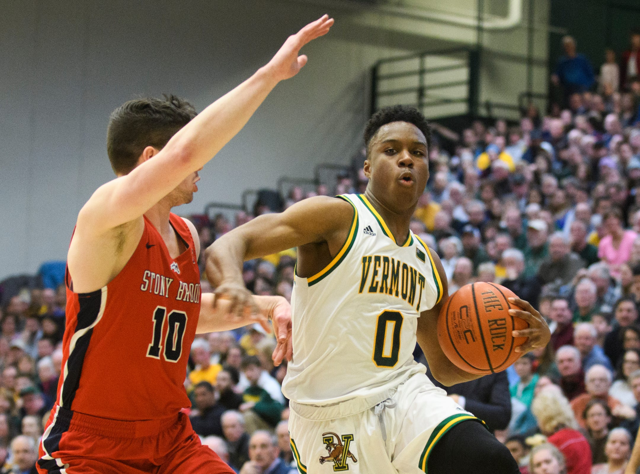 Vermont guard Stef Smith (0) drives to the hoop past Stony Brook's Jordan McKenzie (10) during the men's basketball game between the Stony Brook Seawolves and the Vermont Catamounts at Patrick Gym on Saturday night March 2, 2019 in Burlington, Vermont.