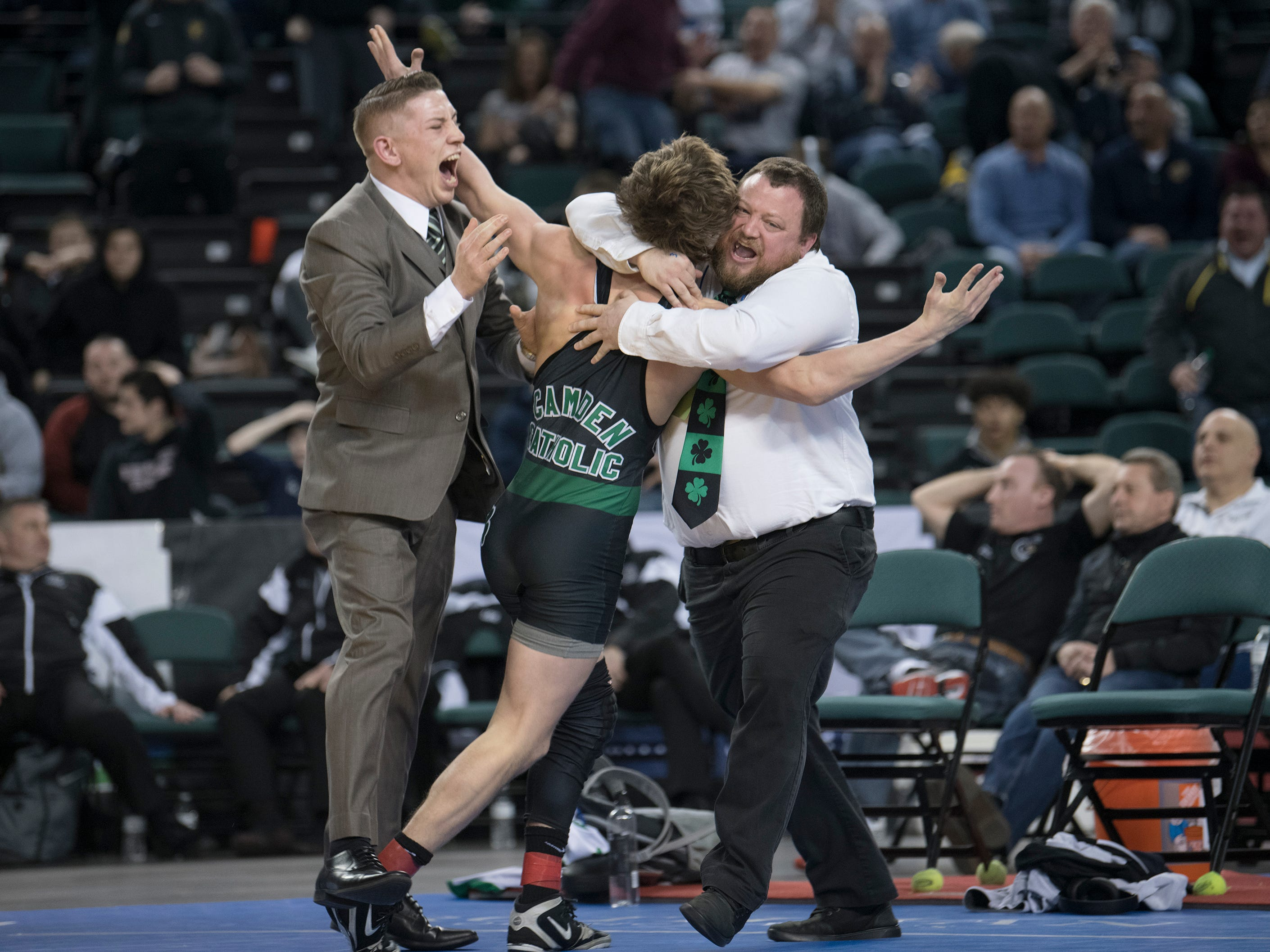Camden Catholic's Lucas Revano celebrates his second state title with his coaches after he pinned DePaul's Ricky Cabanillas in overtime of the 145 lb. championship bout of the 2019 NJSIAA State Wrestling Championships tournament held at Boardwalk Hall in Atlantic City on Saturday, March 2, 2019.