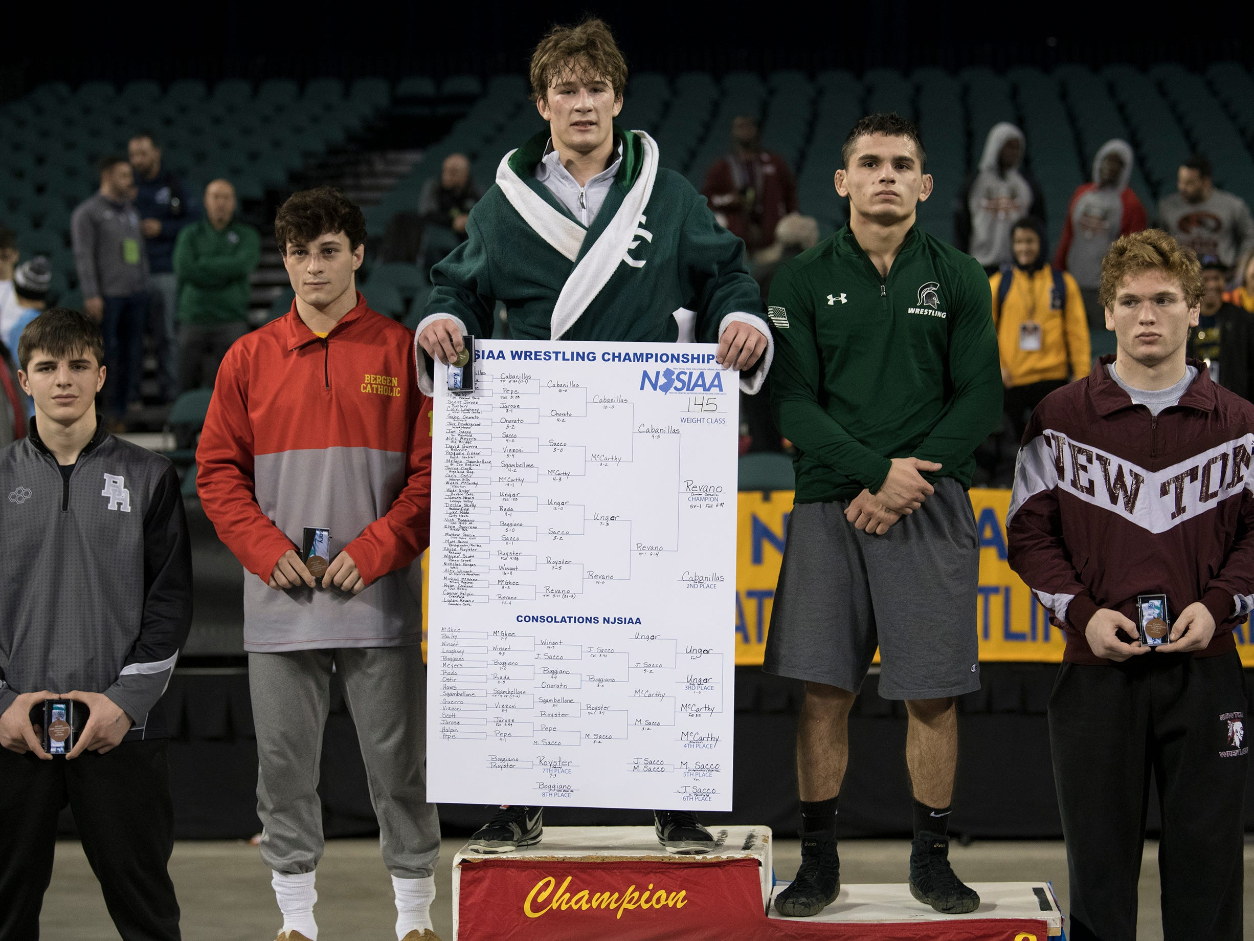 Camden Catholic's Lucas Revano, center, stands a top the podum after he won his second state title by pinning DePaul's Ricky Cabanillas in overtime of the 145 lb. championship bout of the 2019 NJSIAA State Wrestling Championships tournament held at Boardwalk Hall in Atlantic City on Saturday, March 2, 2019.