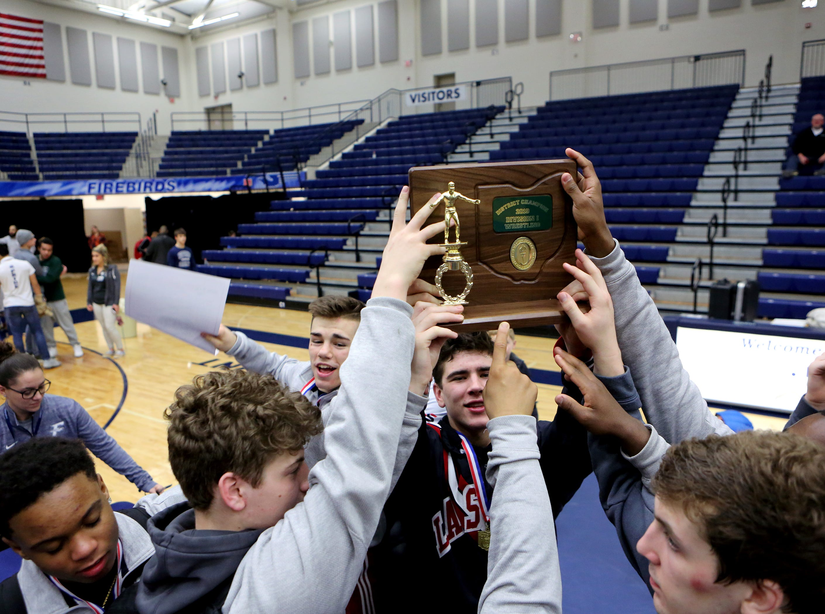 La Salle wrestlers celebrate their overall team championship at the OHSAA Division I Southwest district finals at Fairmont High School Trent Arena.