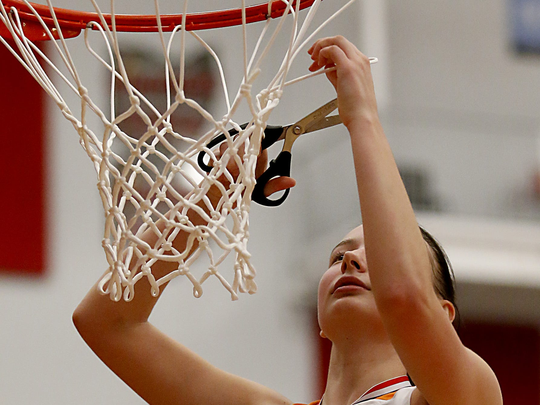 Mercy McAuley's Kieran Casey cuts the net after defeating Mason in their Southwest District Girls Division I finals at Princeton High School in Cincinnati Saturday, Mar. 2, 2019.