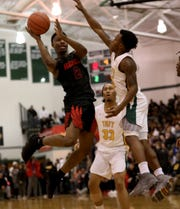 Hughes guard AB Harouna  (2) drives to the basket against Taft guard Demarco Bradley, Saturday, March 2, 2019.