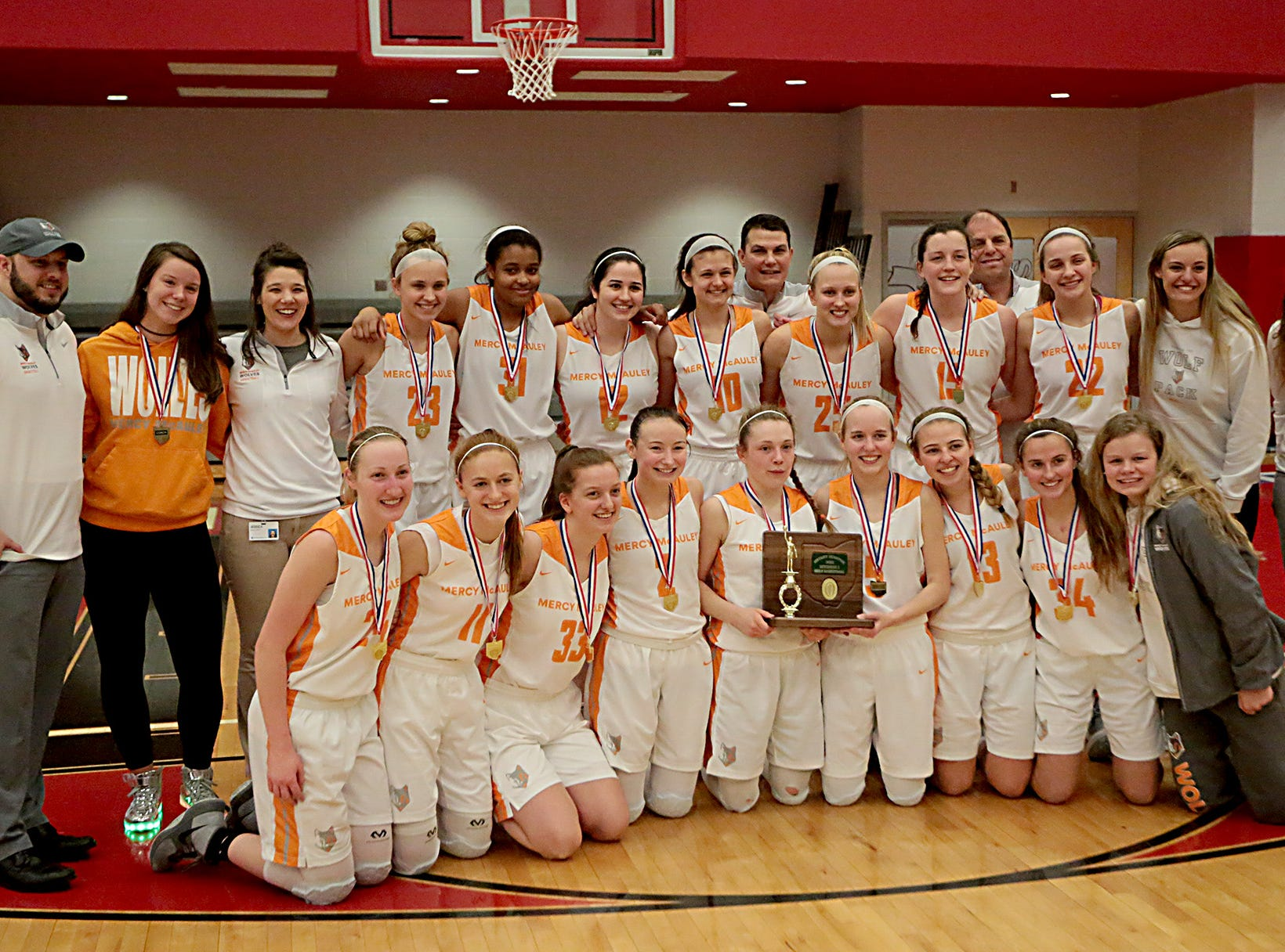 The Mercy McAuley girls celebrate with their trophy after defeating Mason in their Southwest District Girls Division I finals at Princeton High School in Cincinnati Saturday, March 2, 2019.