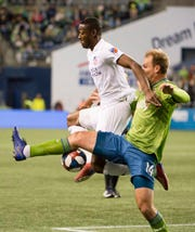 FC Cincinnati forward Fanendo Adi (9) is guarded by Seattle Sounders defender Chad Marshall (14) during the first half at CenturyLink Field.