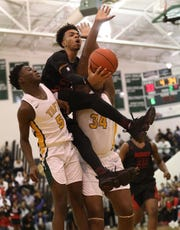 Paul McMillan drives to the basket between Taft players Muhammad Metz and Komari Elam during their tournament game Saturday, March 2, 2019.