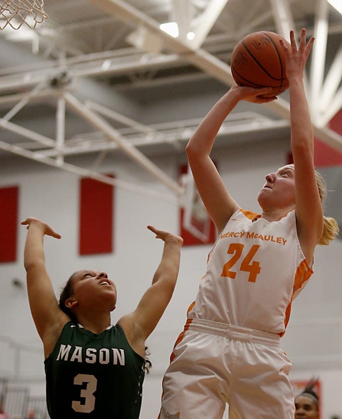 Mercy McAuley's Jenna Schoster puts in two against Mason's Sade Tucker during the Southwest District Girls Division I finals at Princeton High School in Cincinnati Saturday, March 2, 2019. Mercy McAuley beat Mason 50-43 to advance to the regional tournament.