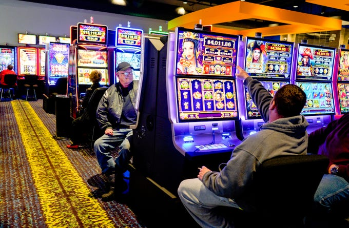 In this Feb. 14, 2019 photo, Terry Christensen of Carter Lake, Iowa, center, plays the slots at the Ponca Tribe's Prairie Flower Casino in Carter Lake, Iowa. Some 150 years after suffering the loss of tribal lands and near-extinction at the hands of the U.S. government, the Ponca Tribe of Nebraska is celebrating a triumph with the opening of a casino intended to secure a stream of revenue for the long-struggling tribe, but is fighting to keep it open in the face of lawsuits by officials in Nebraska and Iowa.