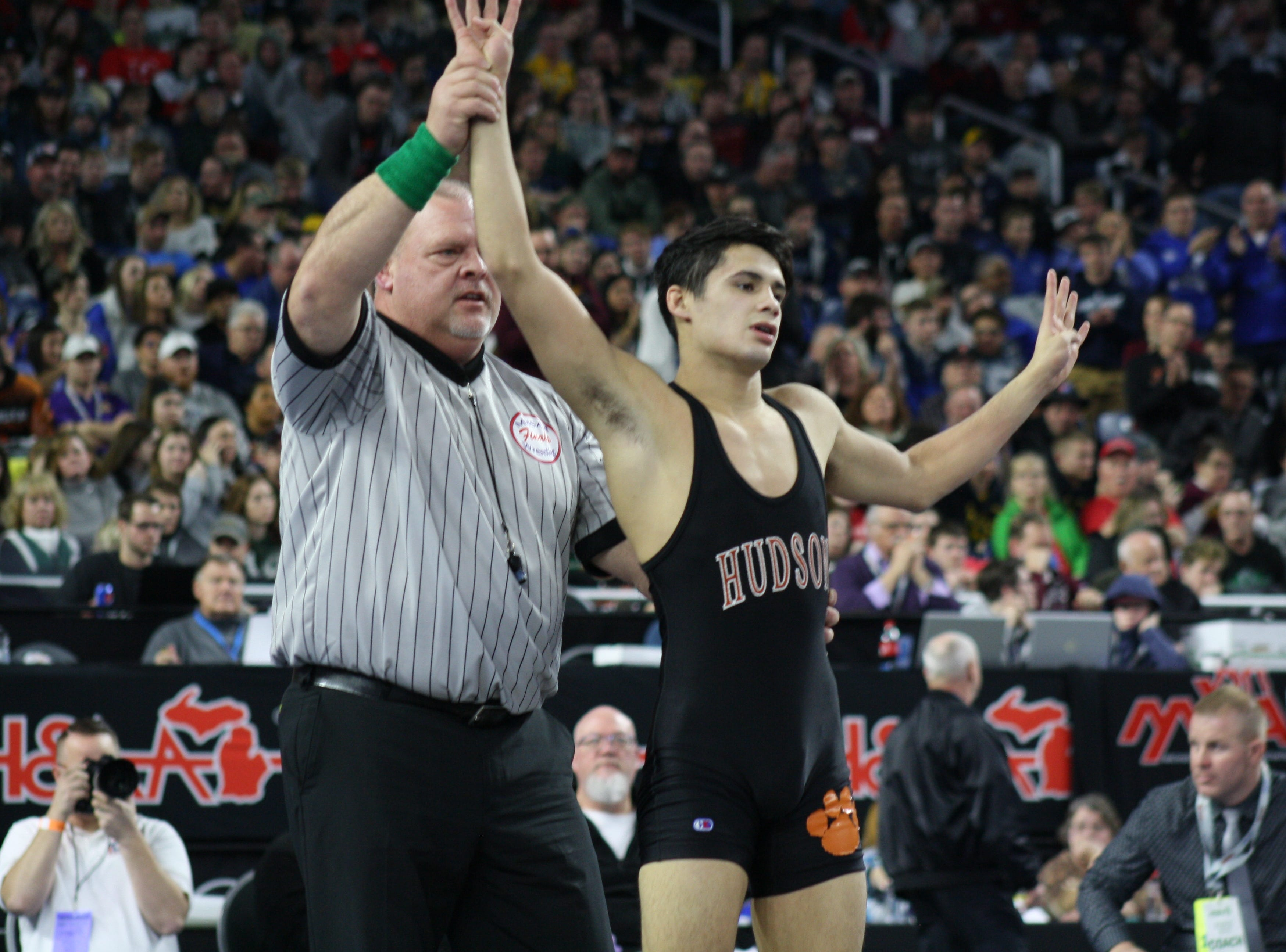 Four-time state champion Jordan Hamdan of Hudson raises four fingers after winning his fourth state championship on Saturday, March 2, 2019 at Ford Field.