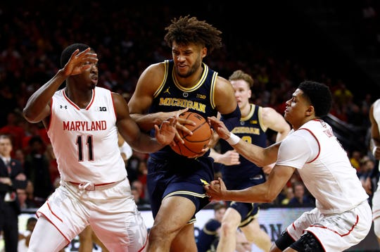 Michigan forward Isaiah Livers drives between Maryland guards Darryl Morsell, left, and Anthony Cowan Jr. in the first half Sunday, March 3, 2019, in College Park, Md.