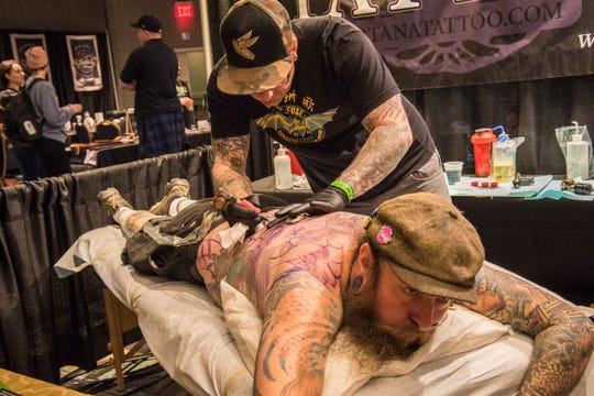 Jeffery Williams rests while tattoo artist Paul Dhuey applies fresh ink Sunday during the 2019 Motor City Tattoo Expo at the Renaissance Center in Detroit.