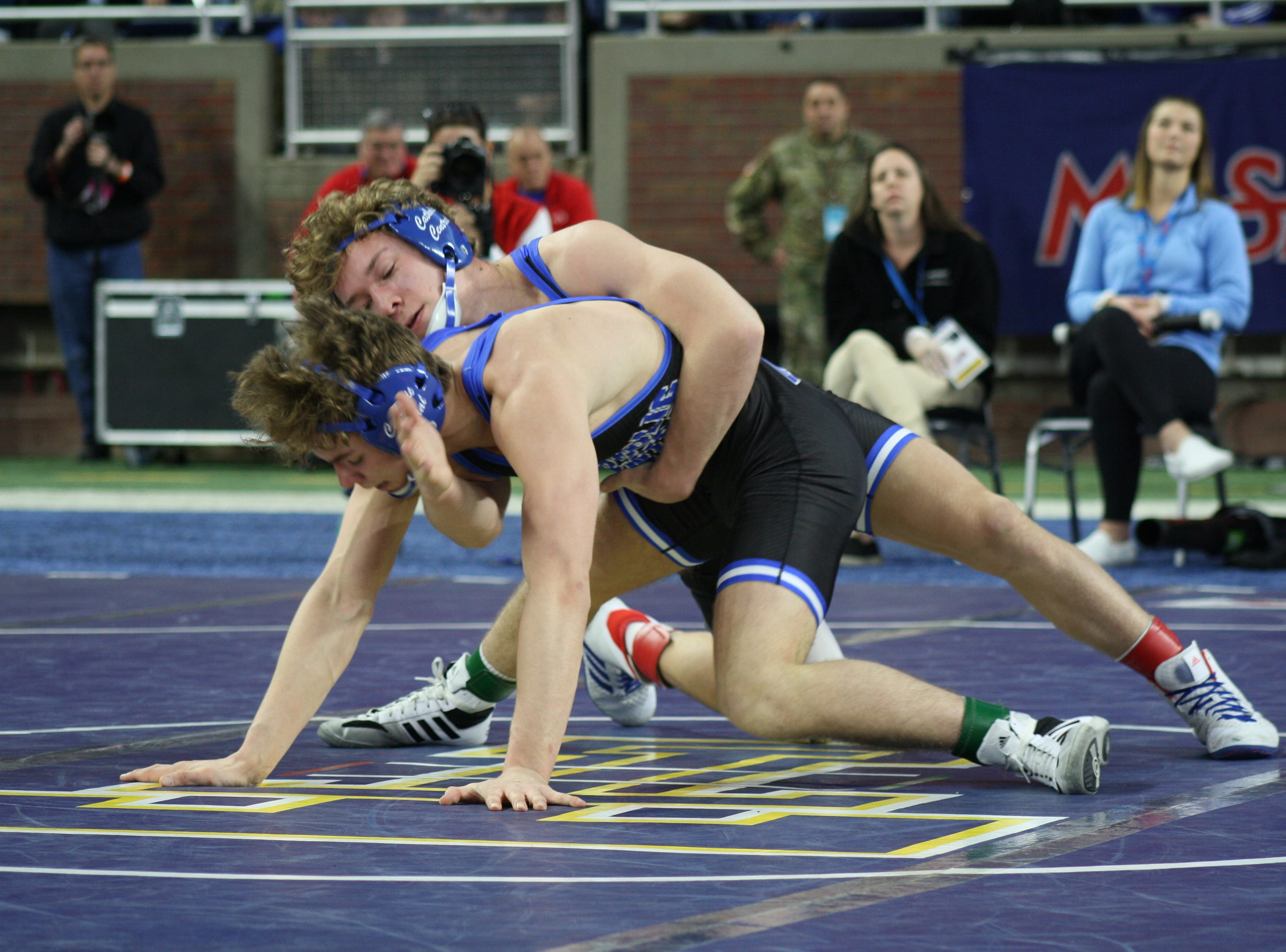 Novi Detroit Catholic Central wrestlers Derek Gilcher (top) and teammate Marc Shaeffer battle it out at 140 pounds, with Gilcher taking a second state title with a 7-2 win.