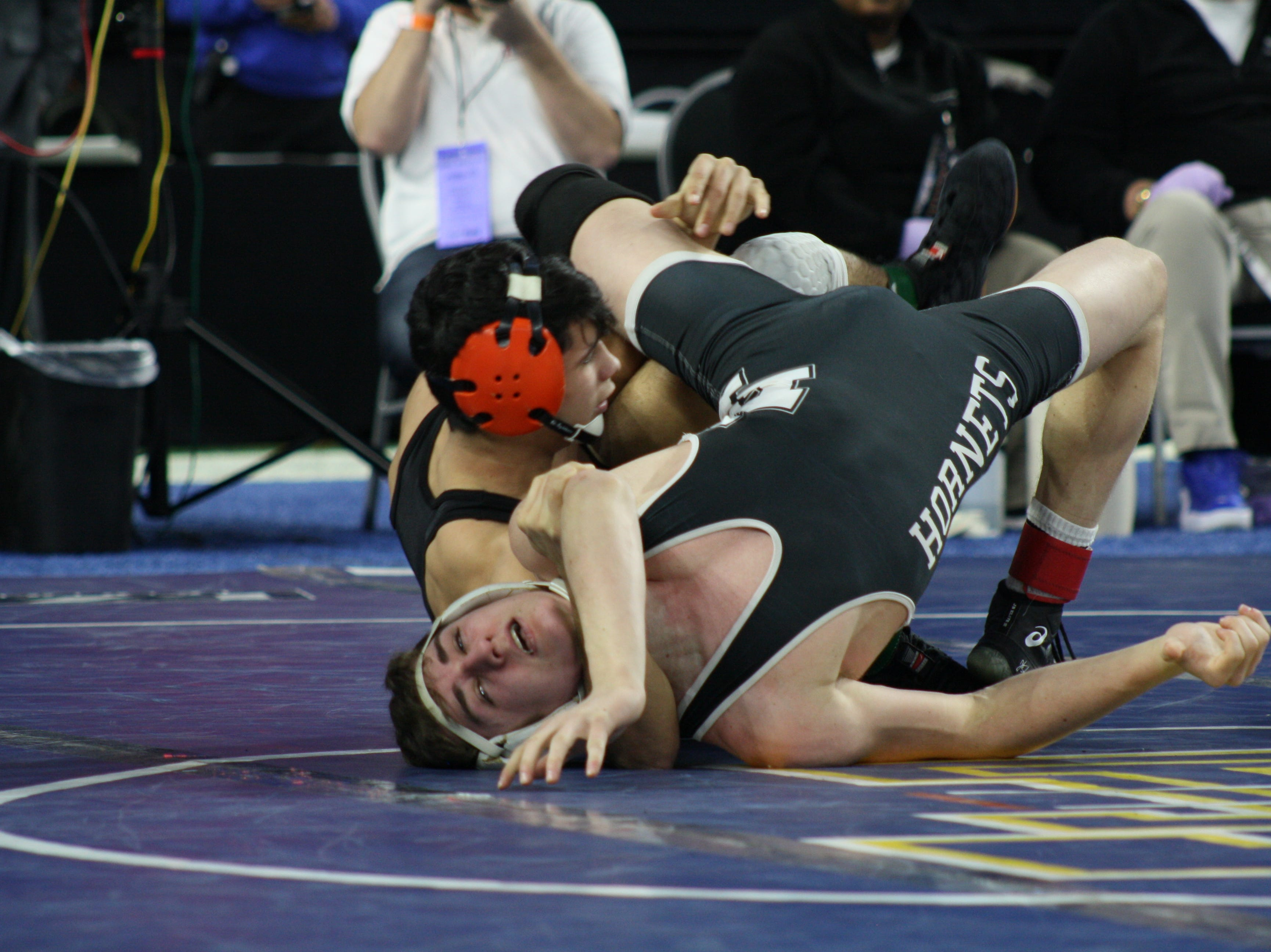 Jordan Hamdan of Hudson (back) takes down his opponent on his way to his fourth-straight state championship.