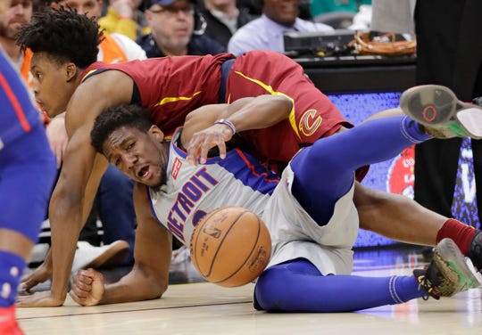 Detroit Pistons' Langston Galloway, bottom, and Cleveland Cavaliers' Collin Sexton battle for a loose ball in the first half.
