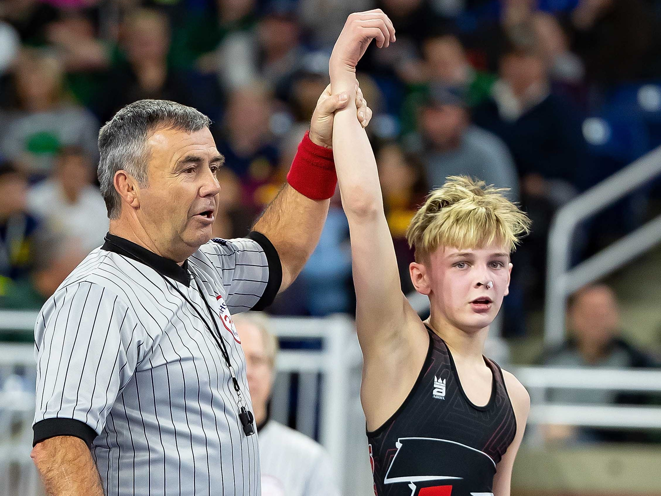 Jamison Zimmerman of Niles raises his arm in victory after defeating  Jacob Brya of St. Johns during their 103-pound Division 2 championship match.