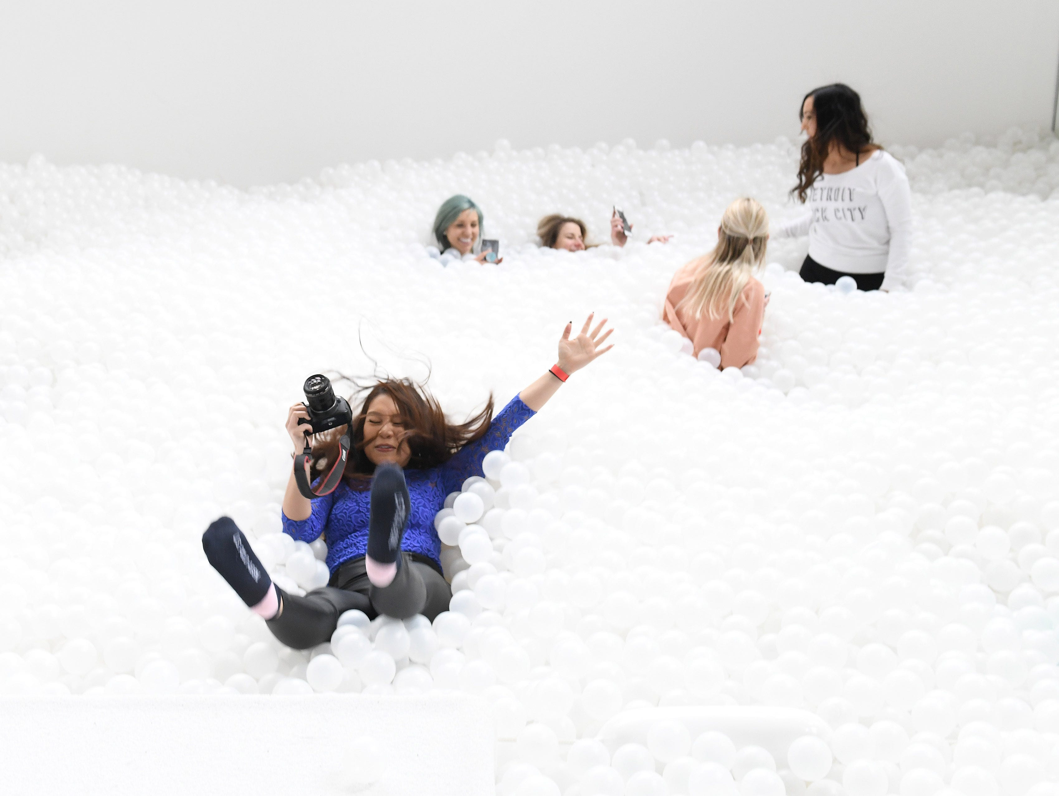 Michelle Nguyen of Detroit falls into the sea of balls at The Beach Detroit.