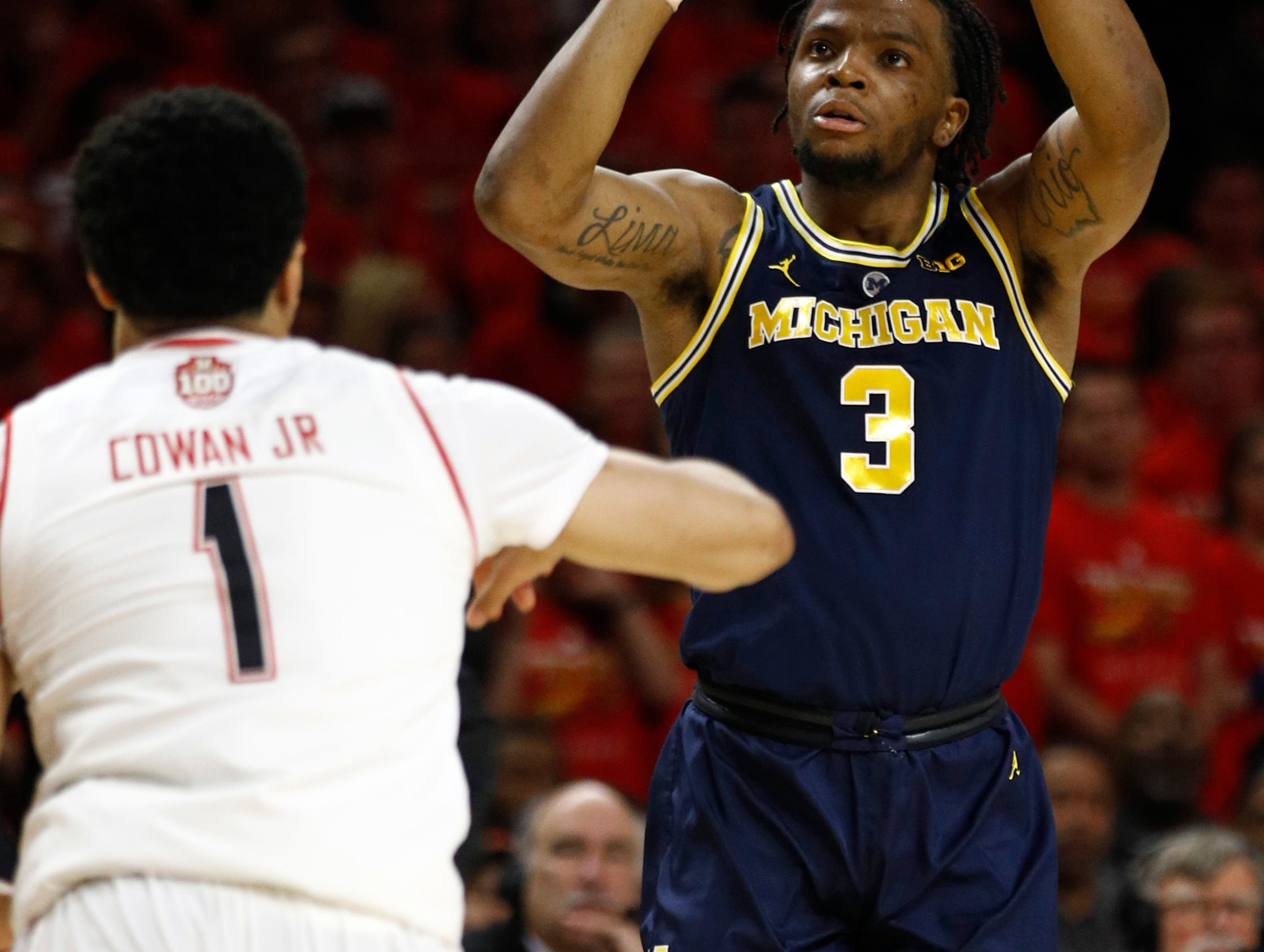 Michigan guard Zavier Simpson, right, shoots over Maryland guard Anthony Cowan Jr. in the first half.