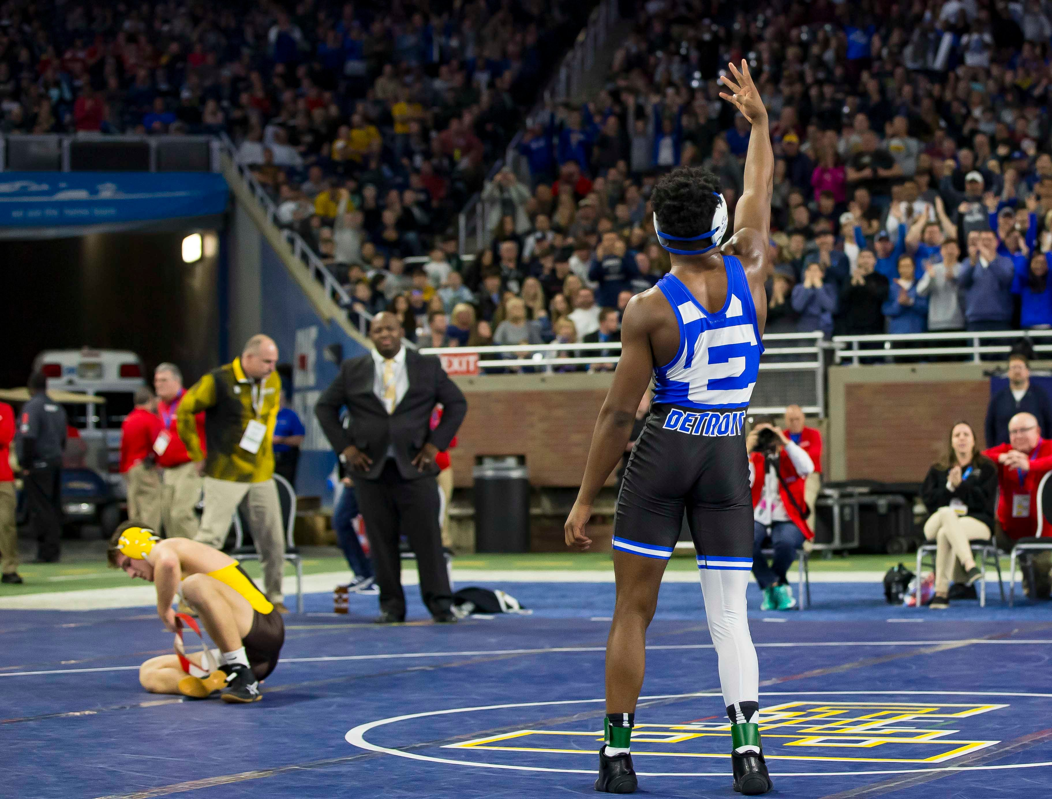 Kevon Davenport of Detroit Catholic Central raises four fingers after winning the 145-pound Division 1 championship match, his fourth straight state championship.