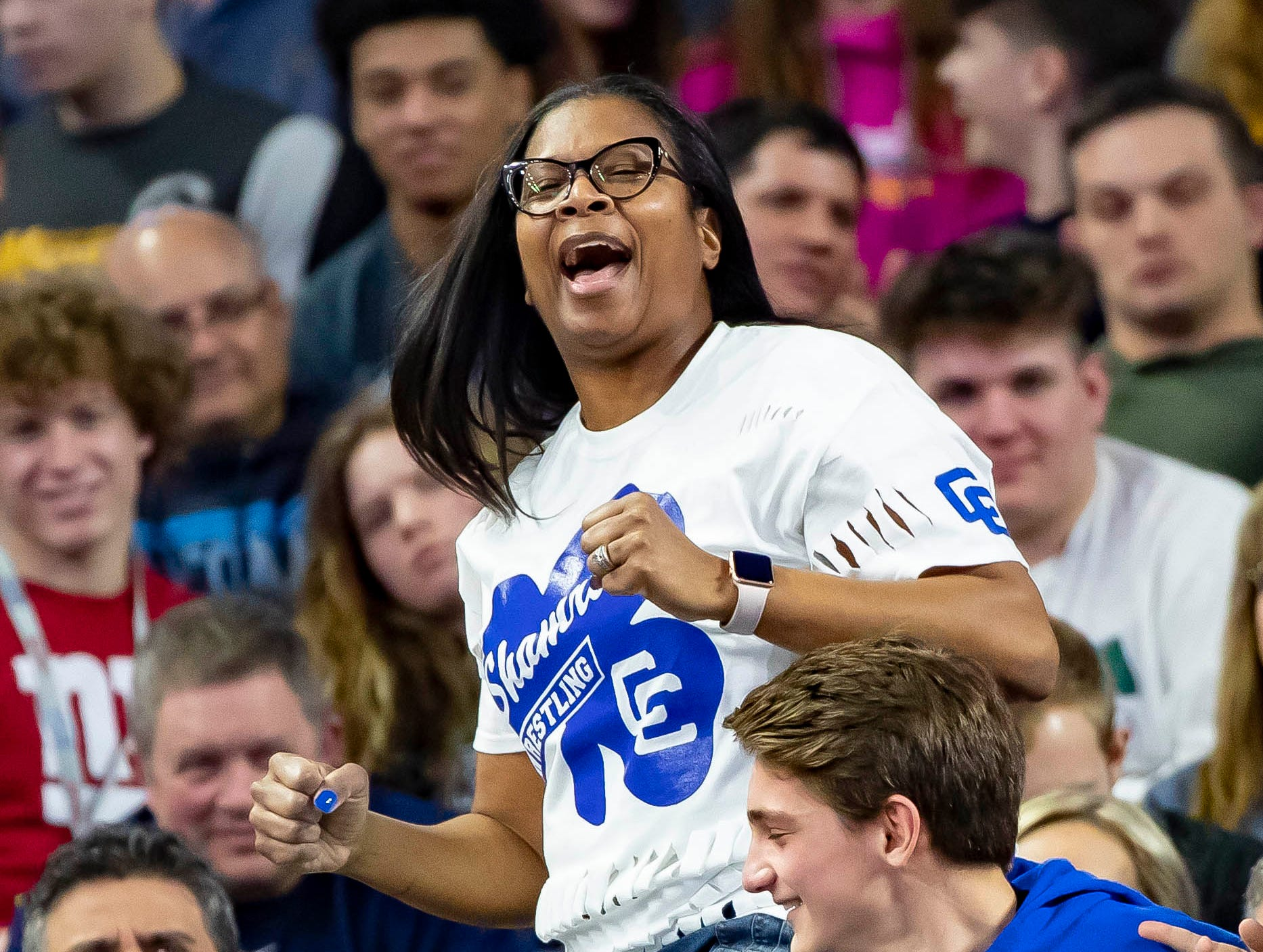 Izetta Davenport, the mother of Kevon Davenport of Detroit Catholic Central, cheers for her son after he defeated Vic Schoenherr of Bay City Western and won his 4th straight state championship.