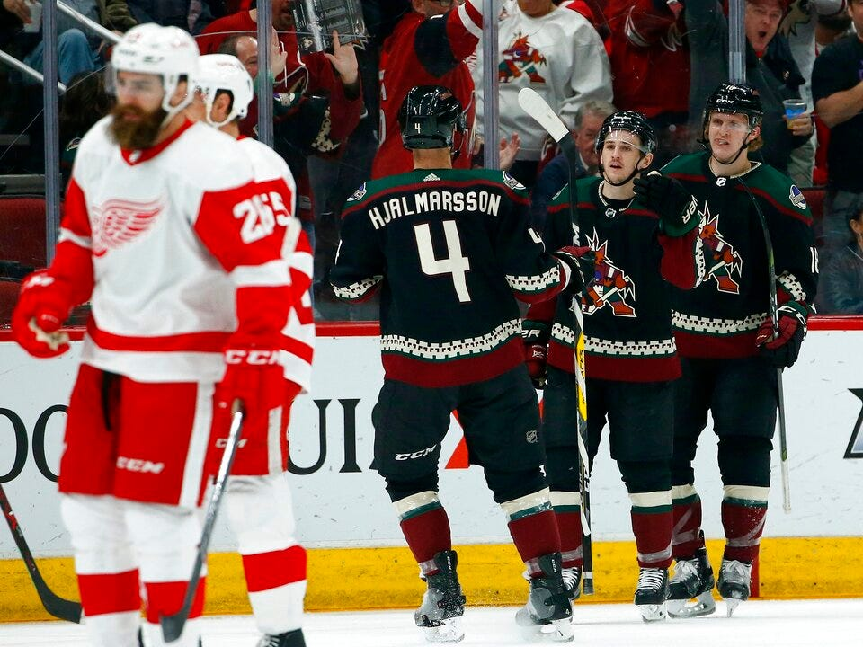 Arizona Coyotes right wing Josh Archibald, second from right, celebrates his goal with Coyotes center Christian Dvorak (18) and defenseman Niklas Hjalmarsson (4) as Detroit Red Wings right wing Luke Witkowski, left, and defenseman Niklas Kronwall, second from left, skate to the bench during the first period.
