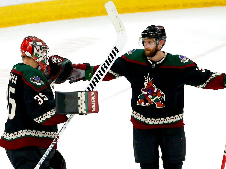 Arizona Coyotes goaltender Darcy Kuemper (35) celebrates a win against the Detroit Red Wings with defenseman Alex Goligoski, right, as time expires in the third period.