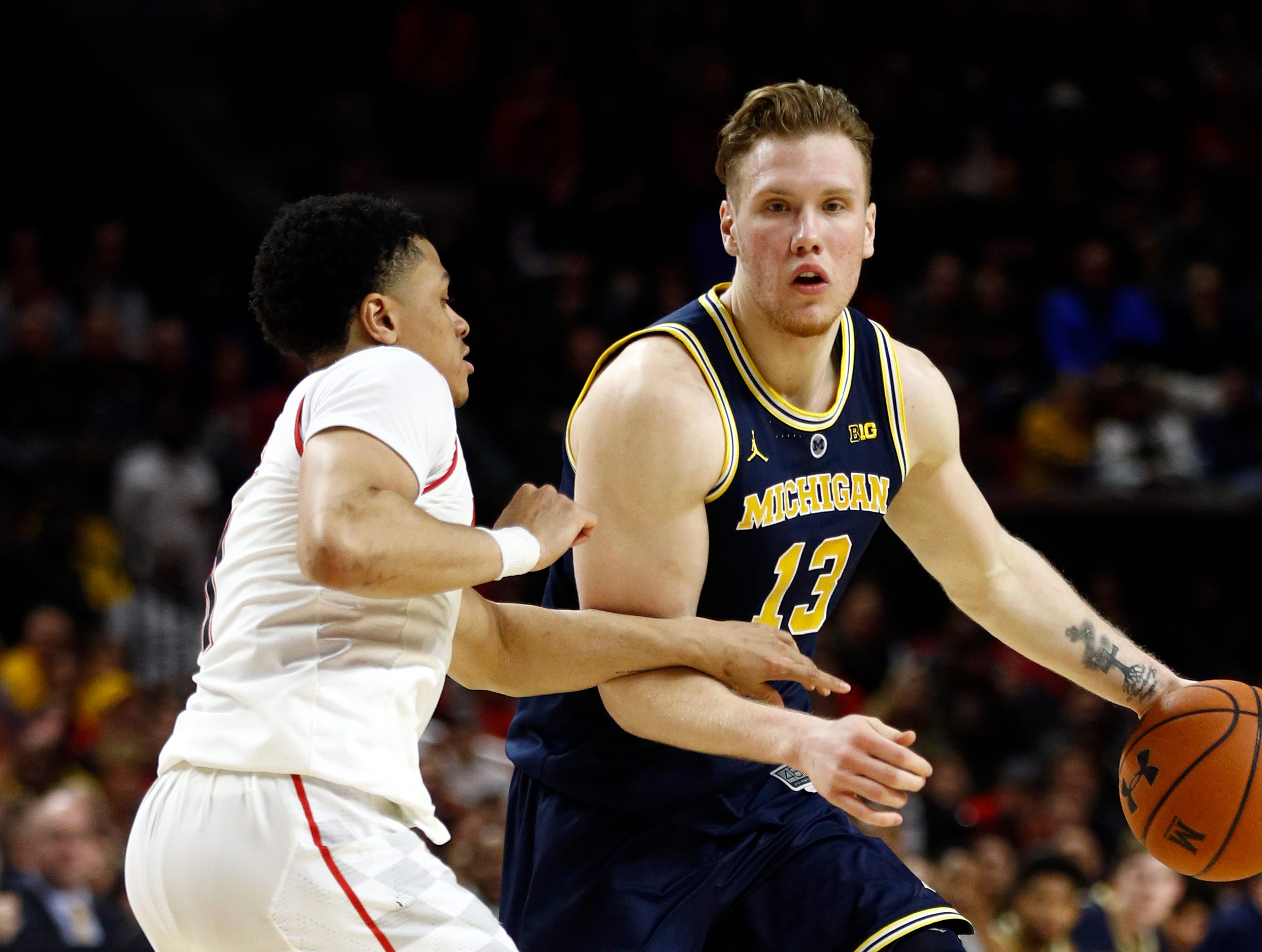 Michigan forward Ignas Brazdeikis, right, of Canada, drives against Maryland guard Anthony Cowan Jr. in the first half of an NCAA college basketball game, Sunday, March 3, 2019, in College Park, Md.