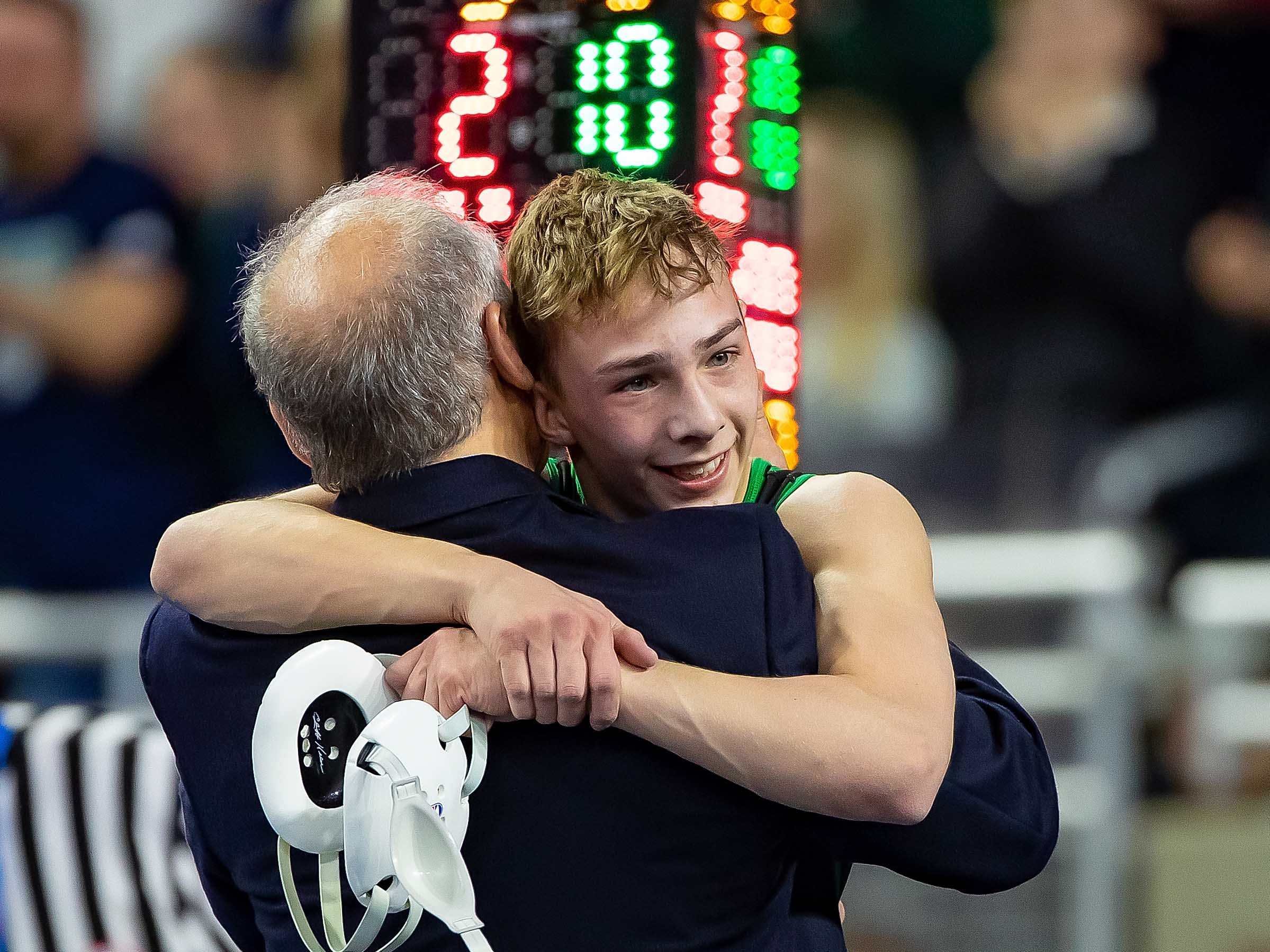Brendan Ferretti of Macomb Dakota hugs his coach after defeating Zein Bazzi of Dearborn Heights Crestwood during their 112-pound Division 1 championship match.