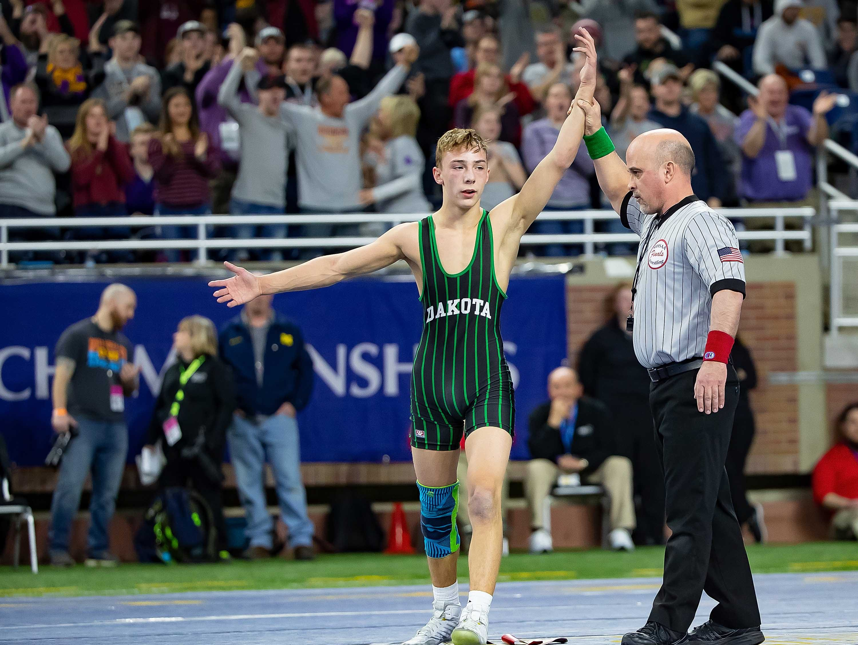 Brendan Ferretti of Macomb Dakota raises his arm in victory after defeating Zein Bazzi of Dearborn Heights Crestwood during their 112-pound Division 1 championship match.